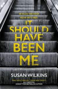 Image of the cover foe It Should Have Been Me by Susan Wilkins. A escalator in the underground travelling upwards showing the feet and lower legs of a lone female portraying a sense of jeopardy
