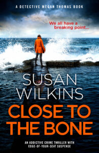 Image of book cover Close To The Bone by Susan Wilkins. A lone female figure standing on a causeway waves crashing around her